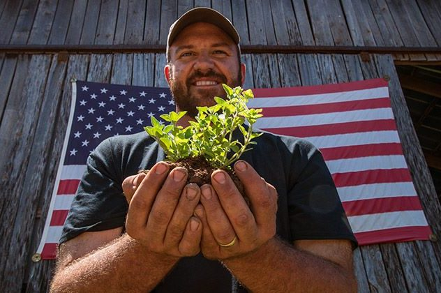 Photo of a veteran carrying a plant in his hands